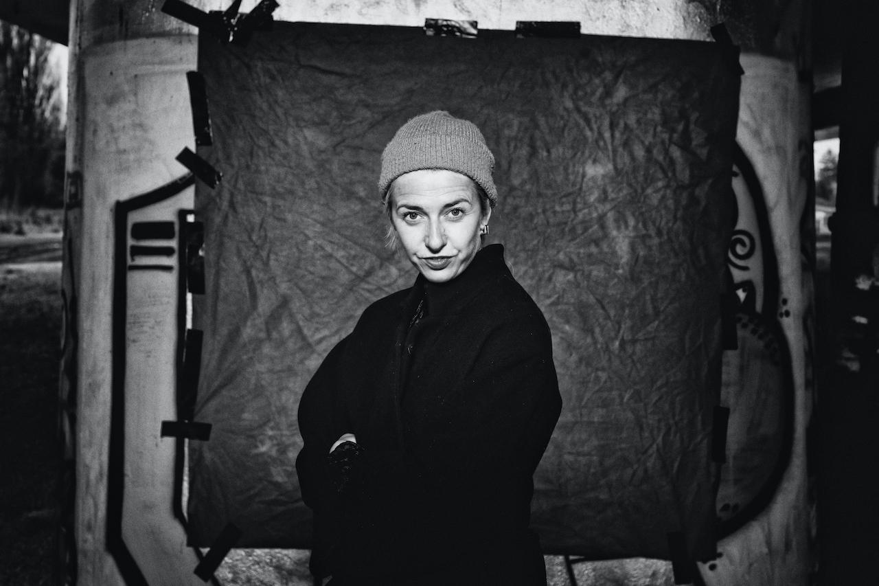 Czarno-biała fotografia, na której znajduje się Justyna Sobczyk. Widzimy ją od pasa w gorę. Ma założone o siebie ręce. Ubrana na czarno. Jest w czapce. Patrzy na nas zadziornie. Stoi na tle szarego prostokąta.