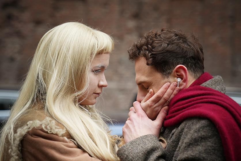 Na zdjęciu kobieta i mężczyzna w planie średnim. Kobieta dotyka czule twarzy mężczyzny. On przytrzymuje jej ręce przy swojej twarzy. Kobieta ma długie blond włosy. Mężczyzna jest brunetem. Ma przewieszony bordowy szal