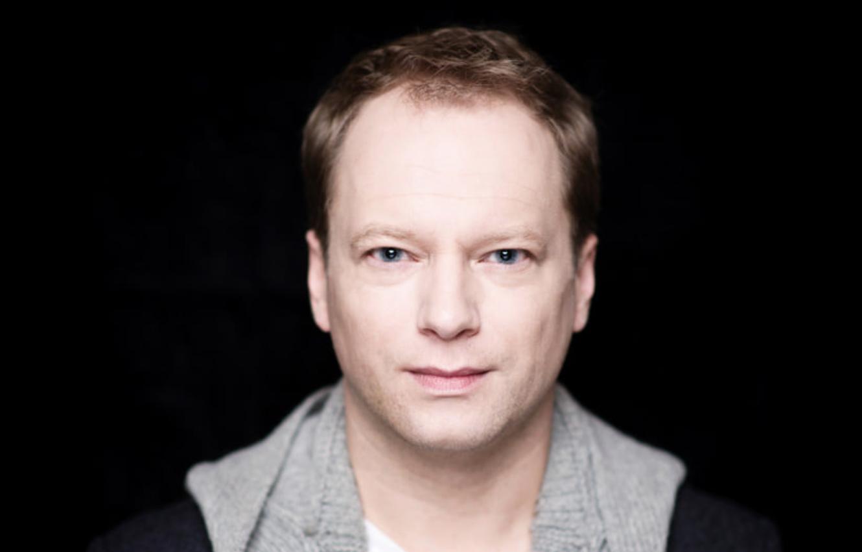 Delikatnie uśmiechnięty Maciej Stuhr na czarnym tle. Portret.