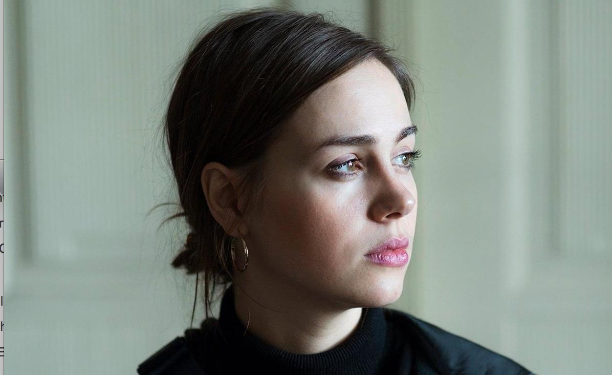 Katarzyna Minkowska zamyślona. Patrzy w kierunku światła. Portret.