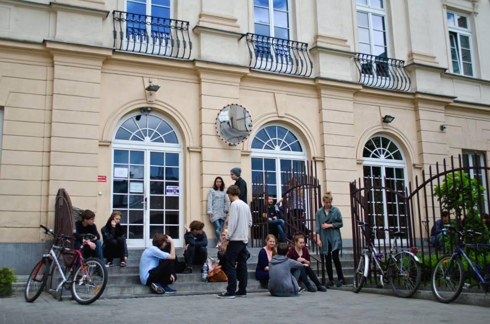Wejście do budynku Akademii Teatralnej od strony parkingu. Przed wejściem, na schodach, siedzą i stoją młodzi ludzie - czekają na swój egzamin. Wokół nich stoją rowery.