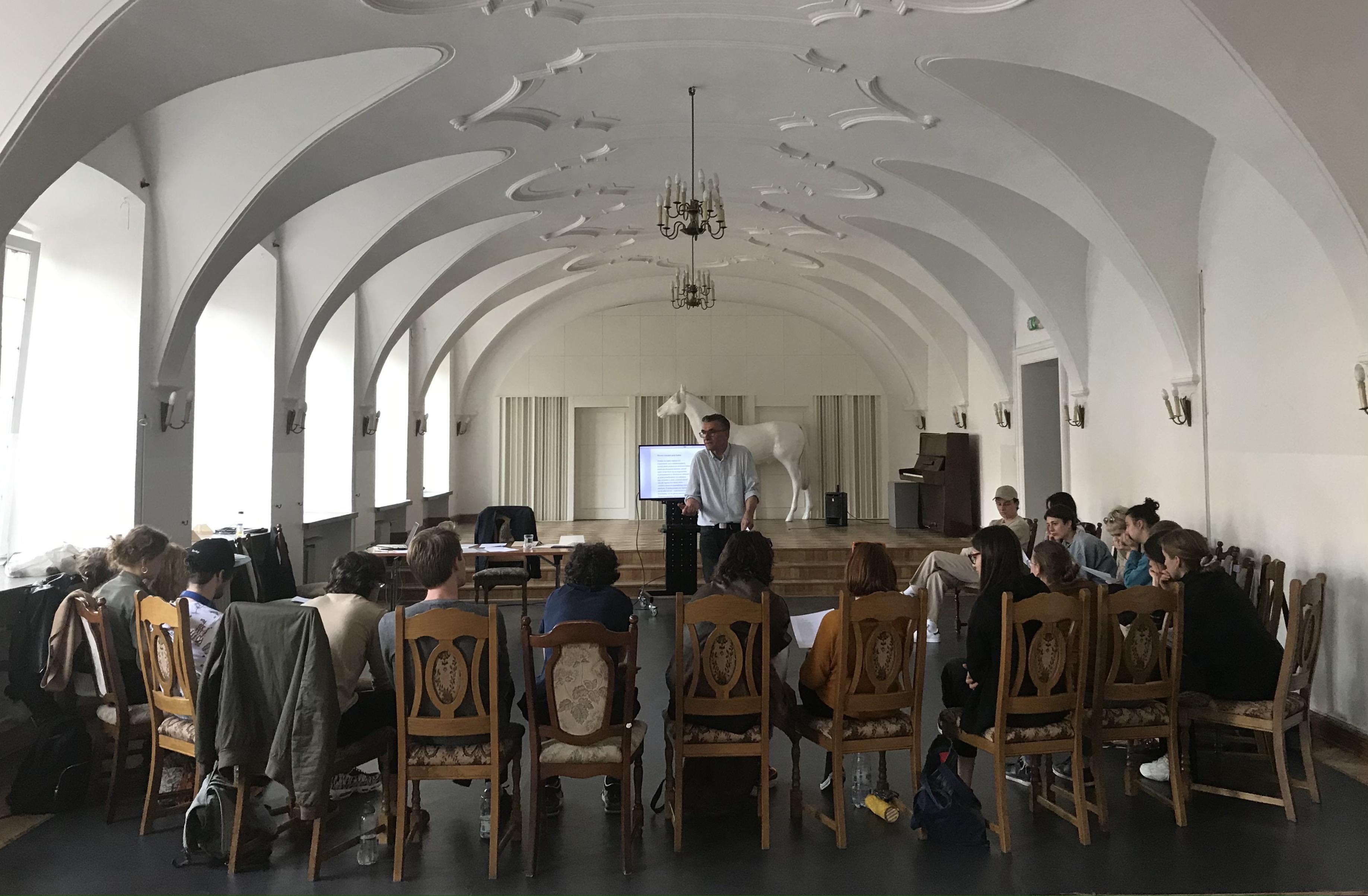 Na środku przestronnej ijasnej sali, stoi mężczyzna wśrednim wieku zkartką, któryprzemawia. Zanim telewizor zwyświetlonym tekstem. Słuchają go, siedzący przednim, młodzi ludzie.